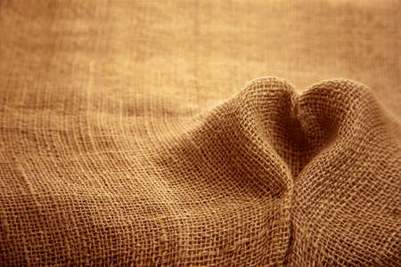 Rustic jute sackcloth fabric textile texture folded in heart shape backdrop