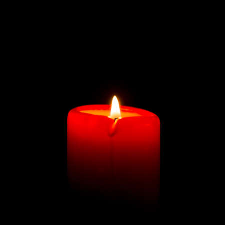 Red candle is burning on a black background