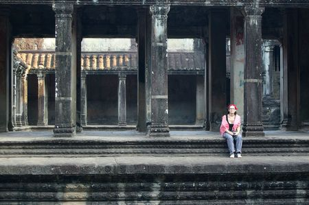 cambodia sculpture: backpacker girl sitting in the empty ruins ruins of angkor wat
