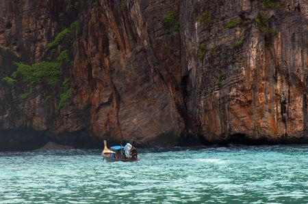 cliff face: small thai fishing boat dwarfed by cliff face