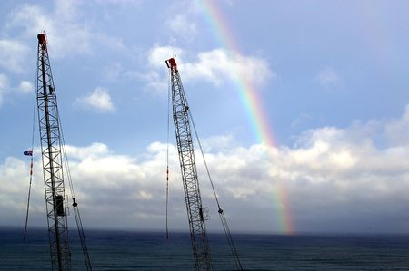 two steel cranes over the beach and rainbow in contrast to nature photo