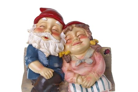 growing together: pair of garden gnomes in love together on chair