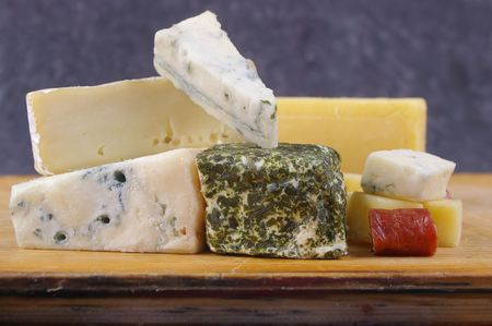 cheese antipasto varieties on wooden chopping board photo