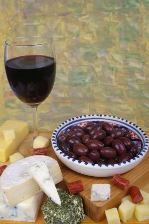 cheese antipasto varieties with olives and wine photo