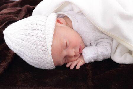 newborn infant baby on fur baby rug having nap time photo