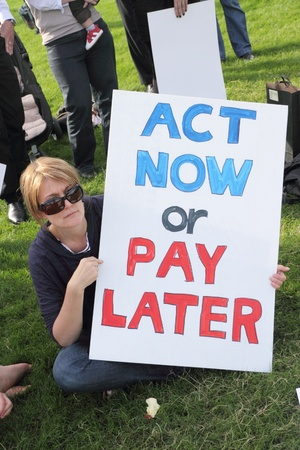 BRISBANE, AUSTRALIA - JUNE 6 : Woman with act now or pay later anti polution sign at say Yes to carbon tax World Enviroment Day protest 6, 2011 in Brisbane, Australia