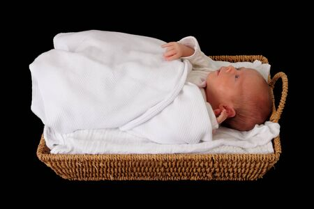 small basket: baby in wicker moses basket isolated over black Stock Photo