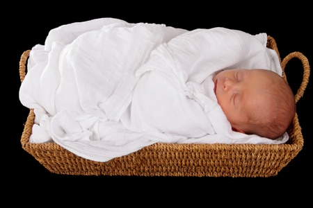 baby in wicker moses basket isolated over black Stock Photo