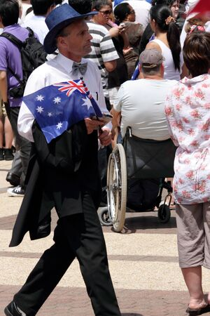 onlooker: BRISBANE, AUSTRALIA  OCT 24 : Onlooker carrying patriotic flag waiting to see Queen Elizabeth 11 October 24, 2011 in Brisbane, Australia