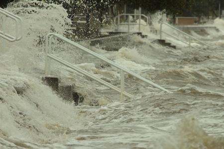 deluge: BRISBANE, AUSTRALIA - JAN 25 : One year on Brisbane flooding again, storm water hitting Sandgate sea wall January 25, 2012 in Brisbane, Australia