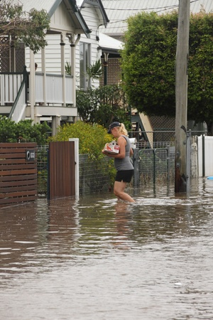 BRISBANE, AUSTRALIA - JANUARY 28 : Unidentified resident taking groceries through flood waters from ex tropical cyclone Oswald on January 28, 2013 in Brisbane, Australia Stock Photo - 17654072