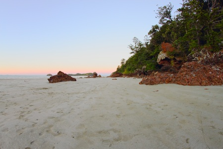whitsunday: volcanic craggy rock beach with norfolk background Hillsborough national park queensland australia