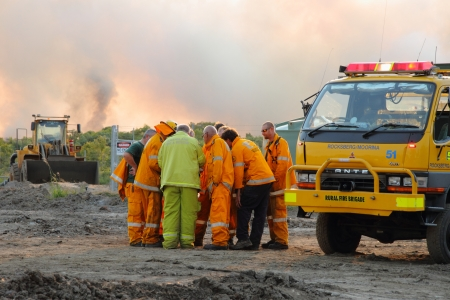 NINGI, AUSTRALIA - NOVEMBER 9   Firefighter crew dicussing approaches to fire front of bush fire November 9, 2013 in Ningi, Australia