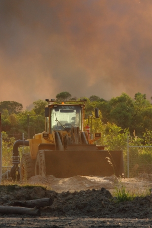 NINGI, AUSTRALIA - NOVEMBER 9   Mining frontend loader with backdrop of approaching bushfire November 9, 2013 in Ningi, Australia