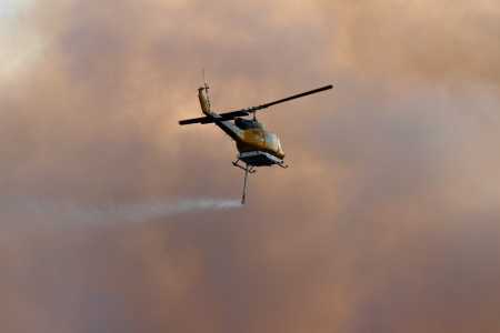 NINGI, AUSTRALIA - NOVEMBER 9   Waterbomber helicopter with full load heading to fire front into clouds of smoke November 9, 2013 in Ningi, Australia