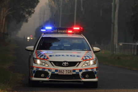 approaches: NINGI, AUSTRALIA - NOVEMBER 9   Police holding cordon in front of bush fire front as it approaches houses November 9, 2013 in Ningi, Australia Editorial