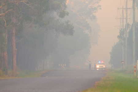 bush fire: NINGI, AUSTRALIA - NOVEMBER 9   Police holding cordon in front of bush fire front as it approaches houses November 9, 2013 in Ningi, Australia Editorial