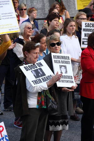 abbott: BRISBANE, AUSTRALIA - JUNE 22 : Unidentified protesters holding anti liberal gonverment and reza berati rememberance signs  attending World Refugee Rally June 22, 2014 in Brisbane, Australia Editorial