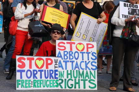 BRISBANE, AUSTRALIA - JUNE 22 : Unidentified protester holding anti goneverment immigration policy sign whilst attending World Refugee Rally June 22, 2014 in Brisbane, Australia