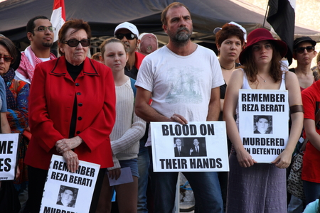 murdered: BRISBANE, AUSTRALIA - JUNE 22 : Unidentified protesters holding anti liberal gonverment and reza berati rememberance signs  attending World Refugee Rally June 22, 2014 in Brisbane, Australia Editorial