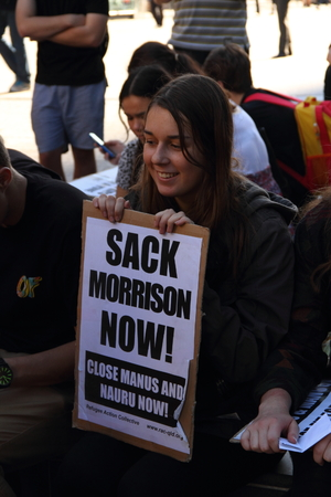 abbott: BRISBANE, AUSTRALIA - JUNE 22 : Unidentified protester with sign to sack immigration minister at World Refugee Rally June 22, 2014 in Brisbane, Australia Editorial