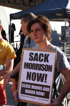 berate: BRISBANE, AUSTRALIA - JUNE 22 : Unidentified protester with sign to sack immigration minister at World Refugee Rally June 22, 2014 in Brisbane, Australia Editorial
