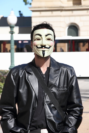 governement: BRISBANE, AUSTRALIA - JULLY 06 : Unidentified protester wearing anonymous mask at Bust The Budget anti liberal governement Rally July 06, 2014 in Brisbane, Australia