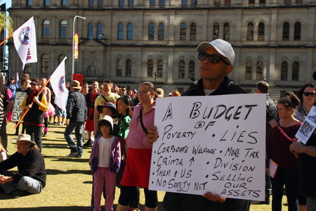 poorer: BRISBANE, AUSTRALIA - JULLY 06 : Unidentified protester with sign showing affected budget groups at Bust The Budget anti liberal governement Rally July 06, 2014 in Brisbane, Australia