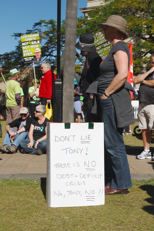 BRISBANE, AUSTRALIA - JULLY 06 : Unidentified protester with sign renouncing priminister Abbott deficits claims at Bust The Budget Rally July 06, 2014 in Brisbane, Australia