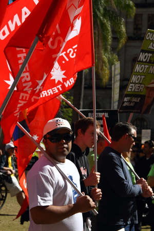 richer: BRISBANE, AUSTRALIA - JULLY 06 : Unidentified protesters with NUW union flags at Bust The Budget anti liberal governement Rally July 06, 2014 in Brisbane, Australia Editorial