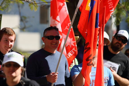 BRISBANE, AUSTRALIA - JULY 06 : Unidentified protesters with NUW union flags at Bust The Budget anti liberal governement Rally July 06, 2014 in Brisbane, Australia
