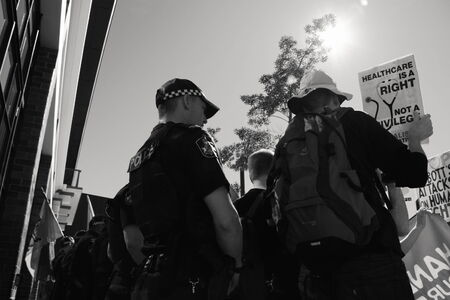 BRISBANE, AUSTRALIA - JULY 12 : Unidentified protesters in front of police cordon outside Liberal National Party national conerfence July 12, 2014 in Brisbane, Australia