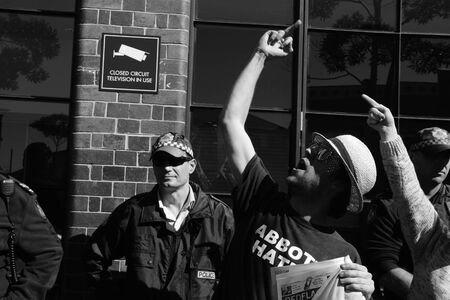 BRISBANE, AUSTRALIA - JULY 12 : Unidentified anti government protester giving primeminister the finger outside Liberal National Party national conerfence July 12, 2014 in Brisbane, Australia
