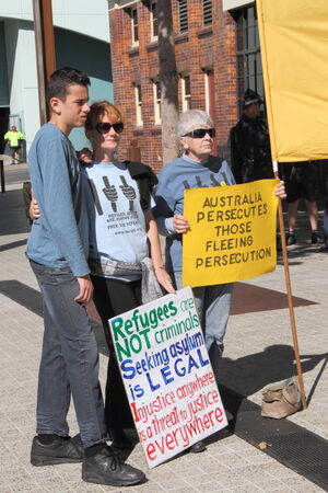 BRISBANE, AUSTRALIA - JULY 12 : Unidentified protesters with anti refugee policy signs outside Liberal National Party national conerfence July 12, 2014 in Brisbane, Australia