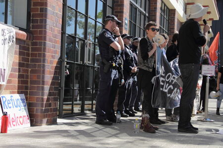 anti fascist: BRISBANE, AUSTRALIA - JULY 12 : Unidentified protesters in front of police cordon outside Liberal National Party national conerfence July 12, 2014 in Brisbane, Australia