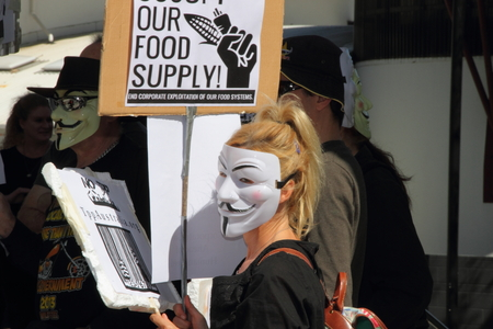 CABOOLTURE, AUSTRALIA - AUGUST 30: Unidentified  anonymous protester with anti Trans-Pacific Partnership agreement sign at March Australia Rally August 30, 2014 in Caboolture, Australia