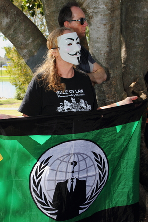 guy fawkes mask: CABOOLTURE, AUSTRALIA - AUGUST 30: Unidentified  anonymous protester with flag at March Australia Rally August 30, 2014 in Caboolture, Australia