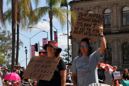 abbott: BRISBANE, AUSTRALIA - AUGUST 31: Unidentified protesters with pro occupy movement policy signs at March Australia Rally August 31, 2014 in Brisbane, Australia