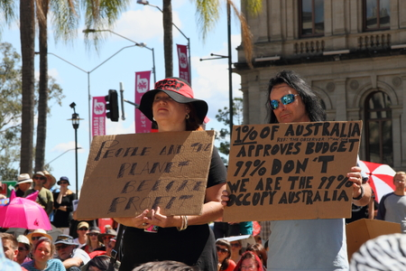 guy fawkes mask: BRISBANE, AUSTRALIA - AUGUST 31: Unidentified protesters with pro occupy movement policy signs at March Australia Rally August 31, 2014 in Brisbane, Australia