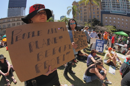 guy fawkes mask: BRISBANE, AUSTRALIA - AUGUST 31: Unidentified protester with pro occupy movement policy sign at March Australia Rally August 31, 2014 in Brisbane, Australia
