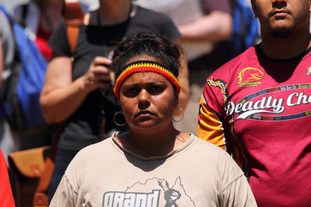 abbott: BRISBANE, AUSTRALIA - NOVEMBER 14: Unidentified protester listneing to speeches during g20 aboriginal deaths in custody protest on November 14, 2014 in Brisbane, Australia