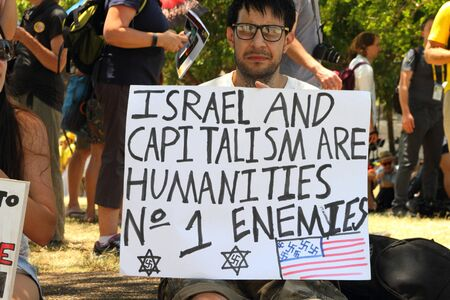 protestor: BRISBANE, AUSTRALIA - NOVEMBER 15: Unidentified protestor with anti Israel and capitalism g20 protest sign on November 15, 2014 in Brisbane, Australia