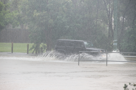 wind force wheel: MORAYFIELD, AUSTRALIA - FEBRUARY 21: Cars driving accross flooded roadway caused by Cyclone Marcia on Feburay 21, 2015 in Morayfield, Australia Editorial