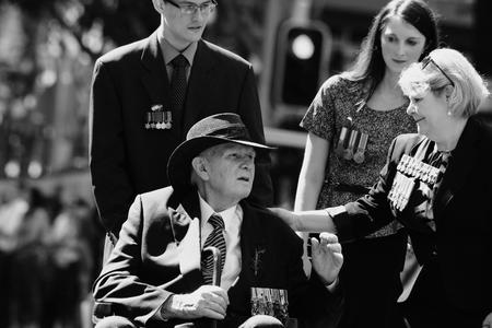 intergenerational: BRISBANE, AUSTRALIA - APRIL 25 : Intergenerational support to older veteran during Anzac day centenary commemorations April 25, 2015 in Brisbane, Australia