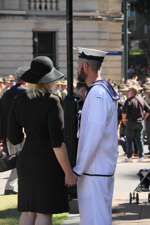spectating: BRISBANE, AUSTRALIA - APRIL 25 : Sailor and partner spectating during Anzac day centenary commemorations April 25, 2015 in Brisbane, Australia Editorial
