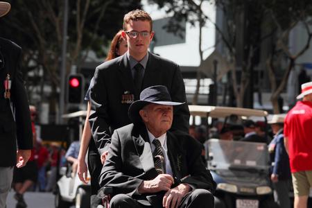 BRISBANE, AUSTRALIA - APRIL 25 : Intergenerational support to older veteran during Anzac day centenary commemorations April 25, 2015 in Brisbane, Australia