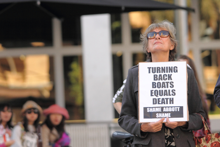 protester: BRISBANE AUSTRALIA  JUNE 20 : Unidentified protester with placard decrying boat turn backs during World Refugee Day Rally June 20 2015 in Brisbane Australia
