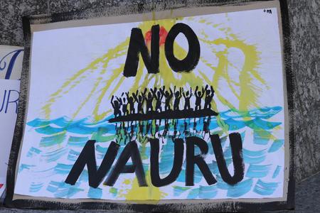 detention: BRISBANE, AUSTRALIA - JUNE 20 : Sign calling for closure of the Naura Island detention center at World Refugee Day Rally June 20, 2015 in Brisbane, Australia