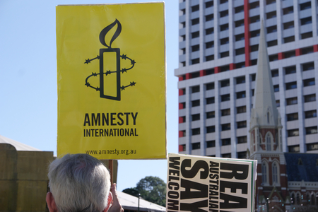 abbott: BRISBANE, AUSTRALIA - JUNE 20: Amnesty International placard at World Refugee Day Rally June 20, 2015 in Brisbane, Australia
