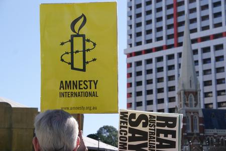 amnesty: BRISBANE, AUSTRALIA - JUNE 20: Amnesty International placard at World Refugee Day Rally June 20, 2015 in Brisbane, Australia